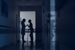 Lady is leaning on doctor and cane in hallway. Woman and physician are standing in hospital corridor. Patient is walking with stick while female practitioner is stock image