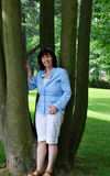 Smiling Chubby Brunette Lady. Woman posing leaning on a large tree with a large green lawn and large trees in the background Stock Photos
