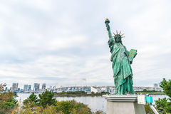 Lady liberty juxtaposed against Rainbow Bridge in Tokyo. Royalty Free Stock Images