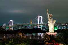 Lady liberty juxtaposed against Rainbow Bridge in Tokyo. Royalty Free Stock Image