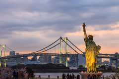 Lady liberty juxtaposed stand at Odaiba and Rainbow Bridge. Royalty Free Stock Images