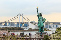 Lady liberty juxtaposed stand at Odaiba and Rainbow Bridge. Royalty Free Stock Photography
