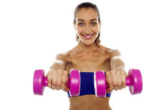 Lady lifting dumbbells, arms outstretched Stock Images