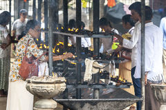A lady lights an oil cup within the Buddhist Temple of the Sacred Tooth Relic complex in Kandy in Sri Lanka. She is amongst thousands of people in Kandy for Royalty Free Stock Photography