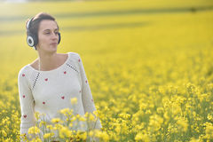Lady listening to music in a canola field Stock Image