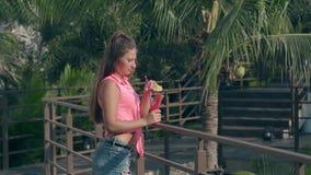 Lady with long brown hair leans on dark bridge railings. Pretty young lady with long brown hair leans on dark bridge railings near green palms on hotel territory stock video
