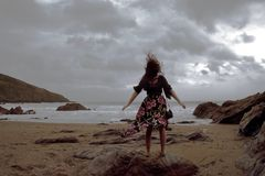Dramatic portrait of long haired lady in floral formal dress on a stormy beach royalty free stock image