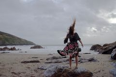 Dramatic portrait of long haired lady in floral formal dress on a stormy beach stock images