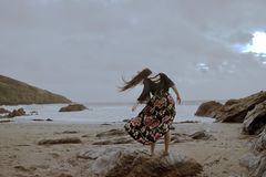 Dramatic portrait of long haired lady in floral formal dress on a stormy beach royalty free stock images