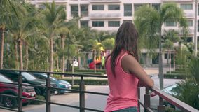 Lady with long hair stands by metal fence and chats. Young lady with long dark brown hair in top and shorts stands by metal fence chatting with friends backside stock video