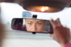 Lady looking back while reversing. Beautiful young lady looking back through the rear view mirror from the front seat of a car while reversing Stock Images
