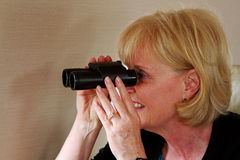 Lady looking through binoculars. Lady holding binoculars and looking Royalty Free Stock Image