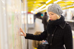Lady looking on public transport map panel. Casually dressed woman wearing winter coat, orientating herself with public transport map panel, pointing on her royalty free stock image