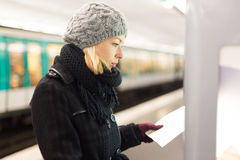 Lady looking on public transport map panel. Stock Photography
