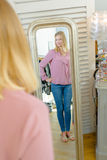 Lady looking at reflection in mirror Royalty Free Stock Photography