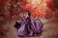 Lady in a luxury lush purple dress. Fantastic shot,fairytale princess is walking in the autumn forest,fashionable toning,creative computer colors royalty free stock photography