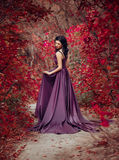 Lady in a luxury lush purple dress. Fantastic shot,fairytale princess is walking in the autumn forest,fashionable toning,creative computer colors Stock Photos