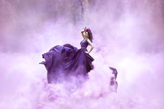 Lady in a luxury lush purple dress. Swirls in the smoke,fantastic shot,fairytale princess is walking in the autumn forest,fashionable toning,creative computer stock photo