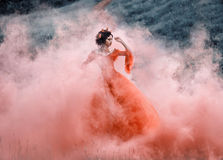 Lady in a luxury lush red dress. Swirls in the smoke,fantastic shot,fairytale princess is walking in the autumn forest,fashionable toning,creative computer Royalty Free Stock Photography