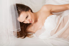 Lady lying in bed wrapped in transparent material Royalty Free Stock Image