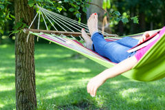 Lady lying with book on hammock Royalty Free Stock Images