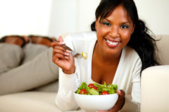 Lady lying on a sofa and eating a vegetable salad Royalty Free Stock Photo
