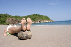 Lady lying tropical beach feet raised on coconut Royalty Free Stock Photography