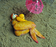 Lady made of chicken on beach food art. Food art of a lady sunbathing on beach, her body made from , an original food-art known as a food-scape, she is made from Royalty Free Stock Image