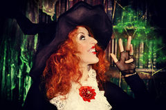 Lady magic. Portrait of a pretty funny witch in the wizarding lair. Fairytales. Halloween royalty free stock images