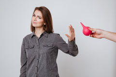 Lady make stop gesture to enema. Image of sick young lady dressed in shirt standing isolated over gray background and make stop gesture to enema Royalty Free Stock Image