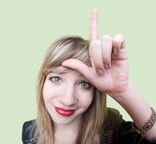 Lady Makes Loser Sign. Cute young Caucasian woman makes loser sign on her forehead over green background royalty free stock photography