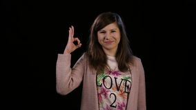 A Lady Making an Ok Gesture. An attractive young lady wearing a pink sweater makes an ok gesture against a black background. Medium shot Royalty Free Stock Photography