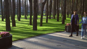 Lady and male walk and talking outdoors. Romantic couple walking on the pavement in spring park with green lawn. Woman and man wearing in casual denim clothes stock footage