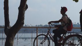 Lady and man bike converge at lake boardwalk. silhouettes. San Pablo City, Laguna, Philippines - October 8, 2015: Lady and man bike together at lake-shore gazebo stock video