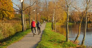 Lady and man bike together at lake shore. Sunny autumn evening.Back view stock footage