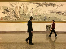A lady and a man passing by a Chinese painting in the Great Hall of People in Beijing. A lady and a man passing by a large piece of traditional Chinese painting Stock Photo