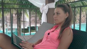Lady with manicure relaxes and surfs internet close view. Interesting young lady with bright trendy manicure and in pink top relaxes and surfs internet close stock video