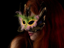 Lady in Mask. Beautiful red-haired young lady in mask on black background Stock Photo