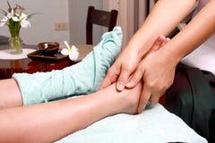 Lady masseur giving patient a leg massage Royalty Free Stock Photos