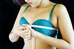 Lady measuring her breast. Picture of a young lady measuring her breast with a tape measure Royalty Free Stock Image