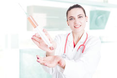 Lady medic showing big syringe Royalty Free Stock Image