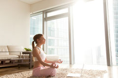 Lady meditating in front of laptop in hotel room Royalty Free Stock Photo