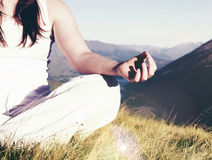 Lady meditating in lotus position on top of the mountain Concept Royalty Free Stock Images