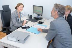 Lady in meeting with middle aged couple. Meeting royalty free stock photography
