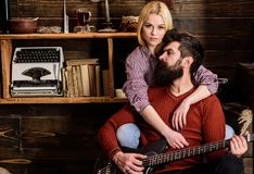 Lady and man with beard on dreamy faces hugs and plays guitar. Couple in wooden vintage interior enjoy guitar music Stock Photos