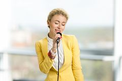 Lady with microphone closed eyes. Young blonde charming woman in formal wear singing on blurred background Royalty Free Stock Images