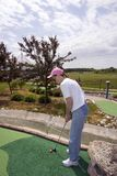 Lady Mini Golfing In The Rough. This mini golf course even has areas of turf that simulate rough Stock Image