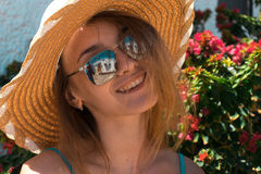 Lady in mirror sunglasses and straw hat smiling on camera outdoors Royalty Free Stock Images