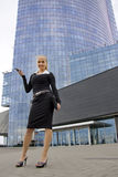 Lady with mobile phone behind modern building. Stock Images