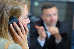 Lady on mobile phone suited man blurred in background stock photography